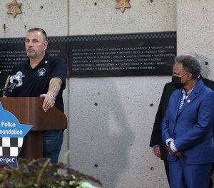 John Catanzara, president of the Chicago Fraternal Order of Police Lodge 7, addresses attendees as Mayor Lori Lightfoot watches during the unveiling of names for five Chicago police officers at the Gold Star Families Memorial and Park in September 2021.