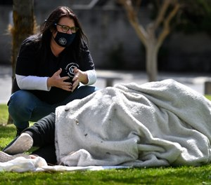 Erin Hishmeh of City Net's Community Care Response Team in Anaheim talks to a woman in La Palma Park in Anaheim who later agreed to accept the help of a shelter.