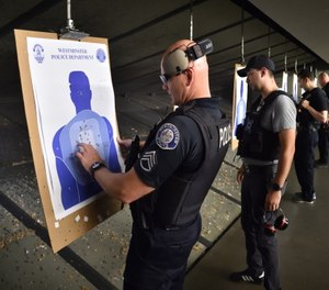 Westminster police officers, including Sgt. Bill Drinnin, left, check their accuracy with live ammunition at an indoor shooting range.