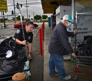 Homeless Liaison Officer Nicole Brown helps Philip bring his laundry to the laundromat.