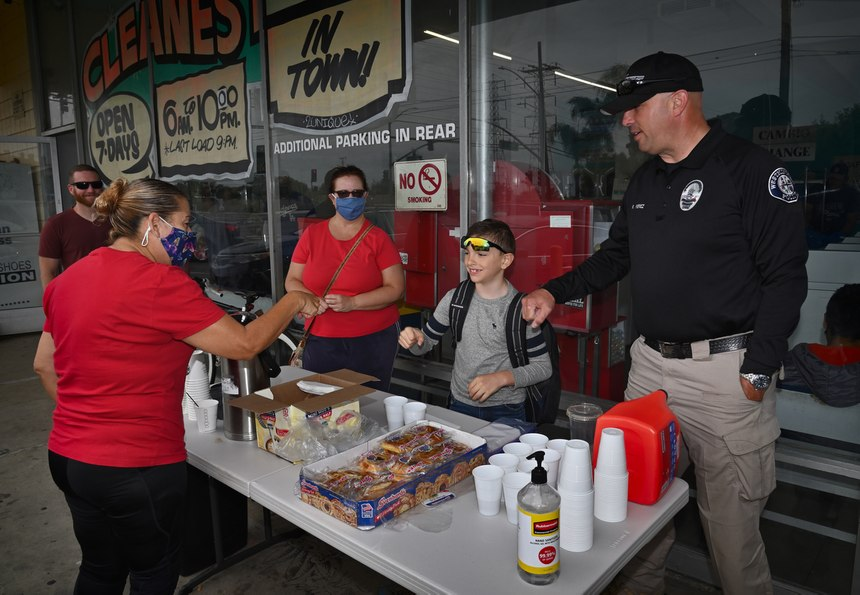 Helping at the table are volunteer Linda Middendof, Aisaiah Perez, 7, and his dad, Westminster Police Department Homeless Liaison Officer Roland Perez, right.
