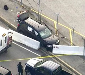 In this image made from video and provided by WUSA TV-9, authorities investigate the scene of a shooting at Fort Meade, Md. on Wednesday, Feb. 14, 2018. A suspect has been held, taken from the black SUV that stopped at barrier after a shooting outside National Security Agency.