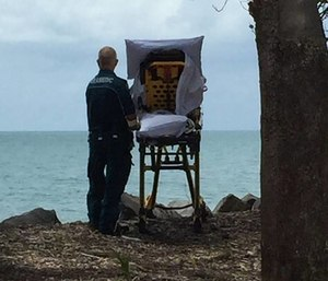 Paramedic Graeme Cooper stands next to a patient's gurney and looking out at the ocean. (Photo/Facebook)