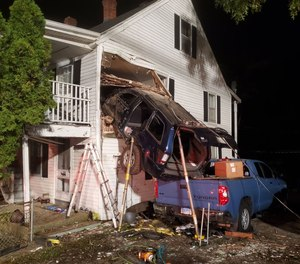 At about1:30 a.m., the East Great Plain Volunteer Fire Company arrived at the scene of the house at665 West Thames St.to find a dark blue SUV stuck nose-first in the upper story of the house, perched on the bed of a pickup truck parked in front.
