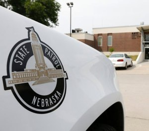 A vehicle with the Nebraska State Patrol logo is parked in a state patrol facility in Omaha, Neb., Wednesday, Aug. 2, 2017. A federal lawsuit accuses the Nebraska State Patrol that it has for years forced female recruits to submit to invasive, medically unnecessary pelvic exams performed by a male doctor before they can be hired. (AP Photo/Nati Harnik)