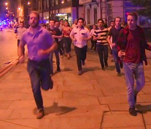 In this image taken from video footage, people run from the scene of attack, alongside a man strolling holding a pint of beer, right, in London, late Saturday, June 3, 2017.