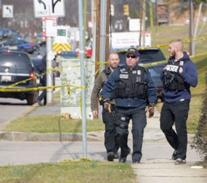 Investigators inspect the area where at least two federal officers were believed to be shot in Northeast Baltimore.