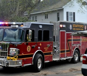 A Stafford firefighter was injured after falling down a 20-foot slope while battling a four-acre brush fire that threatened apartments on Tuesday.
