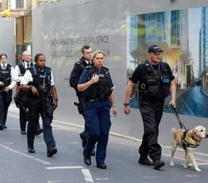 A group of armed British police officers walk with a detection dog after an attack in the London Bridge area of London, Sunday, June 4, 2017.