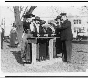 Women police officers inspecting and practicing with handguns.