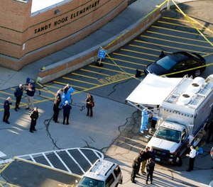 In this Dec. 14, 2012, file photo, officials stand outside of Sandy Hook Elementary School after a shooting in Newtown, Conn.