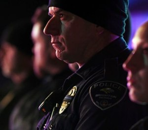 Brighton police officers wear a black ribbon over their badge for Adams County Sheriff's Deputy Heath Gumm in Brighton, Colo., Thursday, Jan. 25, 2018. (John Leyba/The Denver Post via AP)
