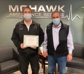 Mohawk Ambulance Service EMT Jesse Strader (left), who is also a volunteer firefighter with the Rexford Fire Department, is presented a Heroism Award by Mohawk Ambulance Service President James P. McPartlon III.