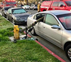 Firefighters broke both back passenger windows of the parked car and snaked the hose through, and eight people were eventually evacuated from the house fire.