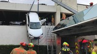 Firefighters rescue woman dangling from parking garage