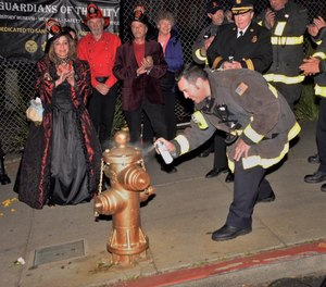 San Francisco firefighters and members of the Guardians of the City of San Francisco historical group spray gold paint onto the hydrant at 20th and Church streets on the 113th anniversary of the Great Earthquake, April 18, 2019. The