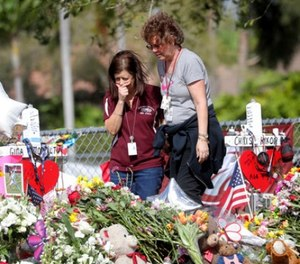 Margarita Lasalle, a bookkeeper and Joellen Berman, a guidance data specialist, look at a memorial Friday, Feb. 23, 2018 as teachers and school administrators returned to Marjory Stoneman Douglas High School for the first time since 17 victims were killed in a mass shooting at the school, in Parkland, Fla.