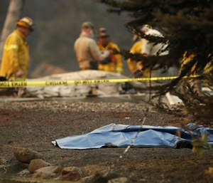 A bag containing human remains lies on the ground as officials continue to search at a burned out home at the Camp Fire.