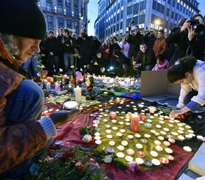 People bring flowers and candles to mourn for the victims at Place de la Bourse in the center of Brussels, Tuesday, March 22, 2016. (AP Image)