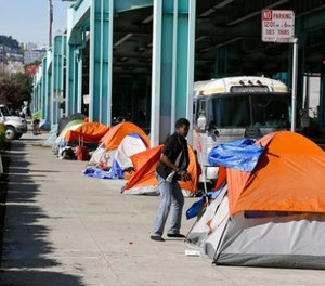 In this Feb. 23, 2016 file photo, a man stands outside of his tent on Division Street in San Francisco. (AP Photo/Eric Risberg, file)