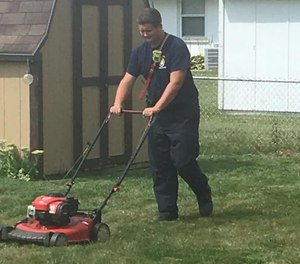Firefighter mows the lawn of a homeowner.