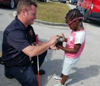 Photos: Firefighter connects with visually-impaired girl during fire safety demo