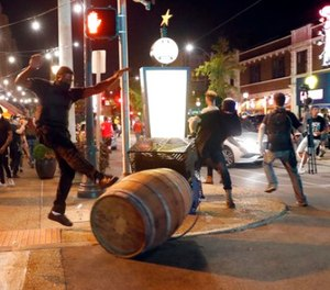 Protesters overturn trash cans as police try to clear a violent crowd Saturday, Sept. 16, 2017, in University City, Mo. (AP Photo/Jeff Roberson)