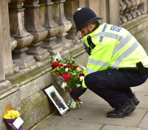 A police officer places flowers and a photo of fellow police officer Keith Palmer, who was killed in yesterdays attack, on Whitehall near the Houses of Parliament in London, Thursday March 23, 2017. (Dominic Lipinski/PA via AP)