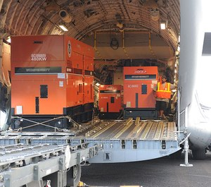 FEMA generators are being unloaded from a C-17 military cargo plane.