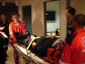 Paramedics wheeling a patient out strapped on a stretcher after injury (image courtesy of Werner Vermaak)