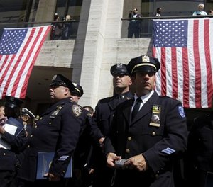 Police officers watch bag pipers play after leaving a ceremony to honor police officers killed during or as a result of the 9/11 terrorist attacks in New York, Thursday, Sept. 8, 2011. (AP Photo/Seth Wenig)
