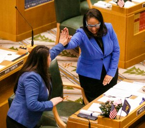 In this Jan. 9, 2017 file photo, Rep. Teresa Alonso Leon and Rep. Janelle Bynum, right, high-five after members of the House of Representatives are sworn into office at the Oregon State Capitol in Salem, Ore. (Molly J. Smith/Statesman-Journal via AP, File)