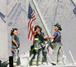 Firefighters raise a flag late in the afternoon on Tuesday, Sept. 11, 2001, in the wreckage of the World Trade Center towers in New York.