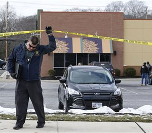 An investigator walks beneath a police tape line at the scene of a shooting at a shopping center in Abingdon, Md., Wednesday, Feb. 10, 2016.