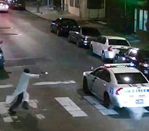 In this Jan. 7, 2016, image made from a video provided by the Philadelphia Police Department, a gunman runs toward a police car driven by Philadelphia police officer Jesse Hartnett in Philadelphia.  (Philadelphia Police Department via AP, File)