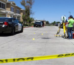 Investigators check a crime scene where two police officers and a burglar were shot on Monday, July 31, 2017, at an apartment complex in Los Banos, Calif. (AP Photo/Scott Smith)