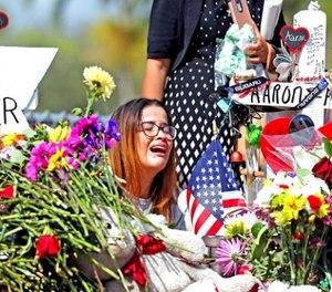 Marjory Stoneman Douglas High School former student Ariana Gonzalez weeps at a cross of slain Marjory Stoneman Douglas coach Aaron Feis, on a hill honoring those killed, Friday, Feb. 23, 2018, in Parkland, Fla. (Charles Trainor Jr./Miami Herald via AP)