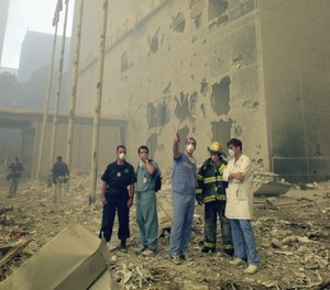 Medical and emergency workers, who are standing in front of the Millenium Hilton, look towards where the World Trade Center towers used to be, after the terrorist attack.