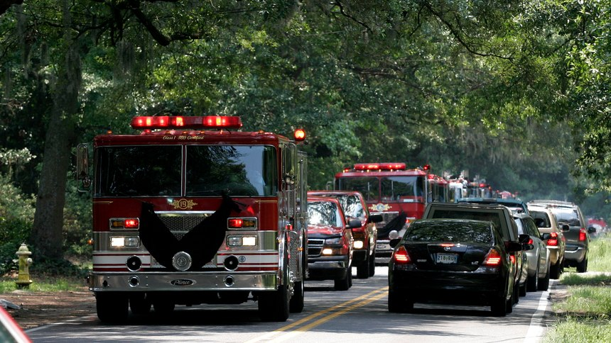 Charleston Fire Department trucks make their way to Pinecrest Baptist Church, in Charleston, S.C., following the public memorial service at the North Charleston Coliseum, on Friday, June 22, 2007, for a private ceremony to pay their final respects to Capt. Billy Hutchinson.