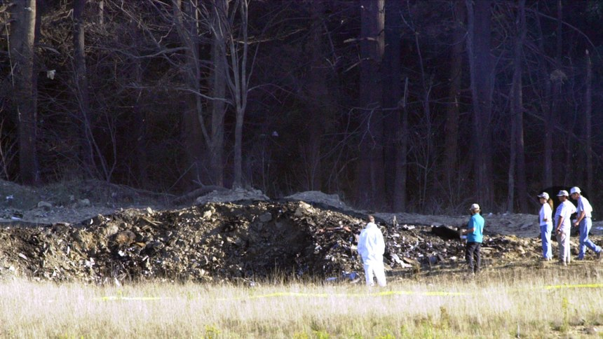 Emergency workers look at the crater created when United Airlines Flight 93 crashed near Shanksville, Pa.