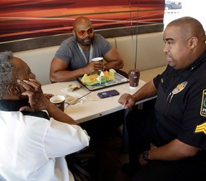 Naomi Parham, left, talks with Miami Gardens police lieutenant Alonzo Moncur, right, during a Coffee with a Cop event, April 27, 2016, in Miami Gardens, Fla.