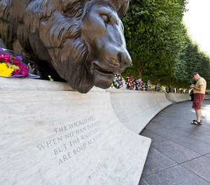 A man looks at the engraved names of fallen law enforcement officers at The National Law Enforcement Officers Memorial in Washington, Friday, July 8, 2016.