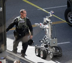 A King County Sheriff bomb disposal unit officer walks near a robotic device near the scene of a shooting involving several police officers in downtown Seattle, Thursday, April 20, 2017.