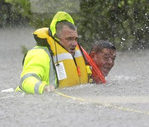 Wilford Martinez, right, is rescued from his flooded car by Harris County Sheriff's Department Richard Wagner. (Photo/AP)