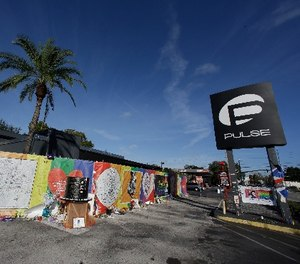 In this Nov. 30, 2016 file photo, artwork and signatures cover a fence around the Pulse nightclub, scene of a mass shooting, in Orlando, Fla. (AP Photo/John Raoux)