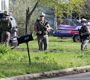 Law enforcement officers secure the neighborhood at the scene of Walnut and 2nd Street in Pflugerville, Texas, on Wednesday, March 21, 2018 where Austin, Texas bombing suspect Mark Anthony Conditt lived. (Tom Reel/The San Antonio Express-News via AP)