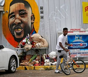 In this June 27, 2017 photo, Ronald Smith gets on his bicycle after stopping at the Triple S Food Mart, where Alton Sterling was shot by police one year ago, in Baton Rouge, La.