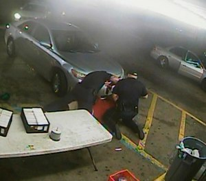 In this still image taken from security camera video provided Friday, March 30, 2018, by the Baton Rouge Police Department, officers Blane Salamoni and Howie Lake II confront Alton Sterling during a struggle outside the Triple S Food Mart in Baton Rouge, La., in July 2016.