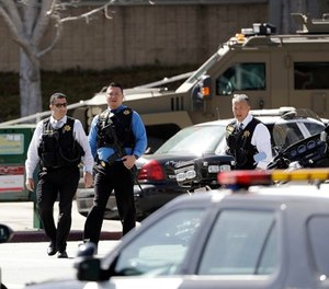Armed law enforcement personnel exit YouTube headquarters, Tuesday, April 3, 2018, in San Bruno, Calif. A woman opened fire at YouTube headquarters Tuesday, setting off a panic among employees and wounding several people before fatally shooting herself, police and witnesses said.