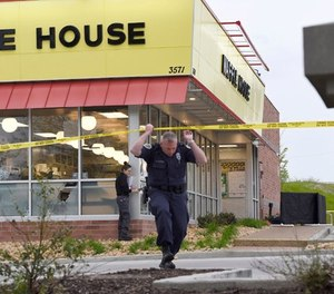 Law enforcement officials work the scene of a fatal shooting at a Waffle House in the Antioch neighborhood of Nashville, Sunday, April 22, 2018.